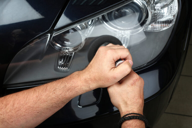 The worker polishes optics of headlights of the car with the electric tool. Close up